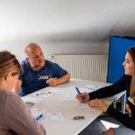 drei Menschen diskutieren in einem Seminarraum